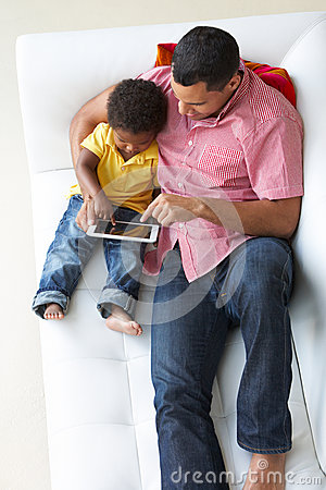 Overhead View Of Father And Son On Sofa Using Digital Tablet
