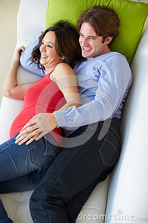 Overhead View Of Man And Pregnant Wife Watching TV On Sofa