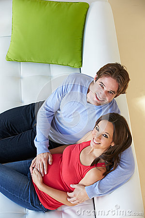 Overhead View Of Man Watching TV On Sofa With Pregnant Wife
