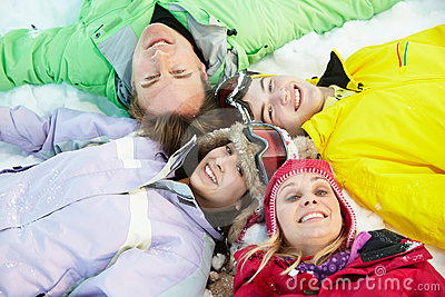 Overhead View Of Teenage Family Lying In Snow