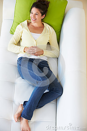 Overhead View Of Woman Relaxing On Sofa Watching Television