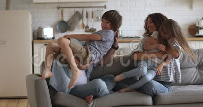 Overjoyed happy family of four enjoying leisure time at home. Hyperactive little boy son climbing on smiling father while attractive young mommy playing with stock footage