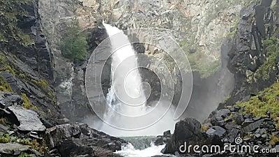 Overvloedig in de diepe waterval Koerkure in de Altai-republiek in Rusland Spray, hooi uit water, koelte en versheid stock video
