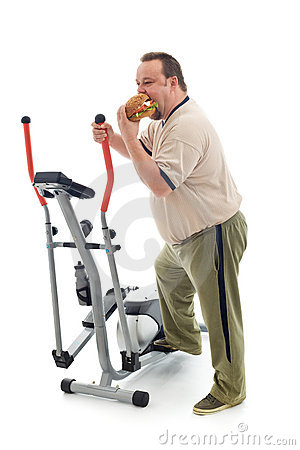 Overweight man eating by an exercising device