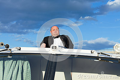 Overweight man in a tuxedo at the helm of a pleasure boat