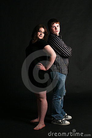 Overweight teenage couple standing back to