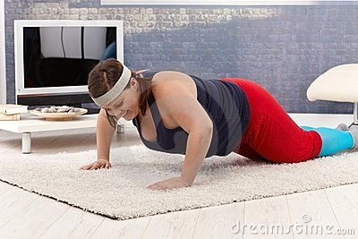 Overweight woman doing push-ups at home