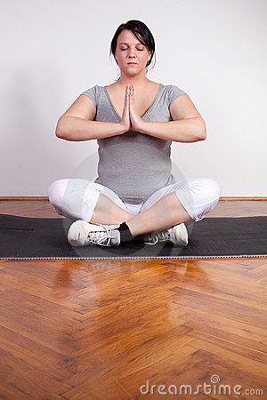 Overweight woman practising yoga