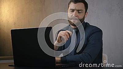 Overwerkte zakenman lost 's avonds problemen op bij het werken aan een laptop, zenuwachtige storing, bedrijfsproblemen stock footage