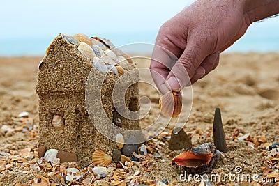 Père construisant une maison de sable sur un bord de la mer