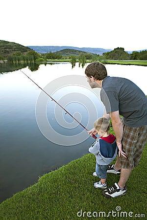 Père enseignant son jeune fils à pêcher.