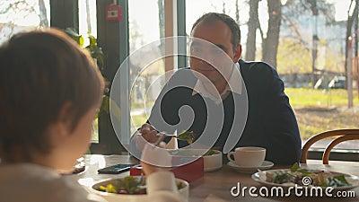 Père parle à son fils pendant le déjeuner au café clips vidéos