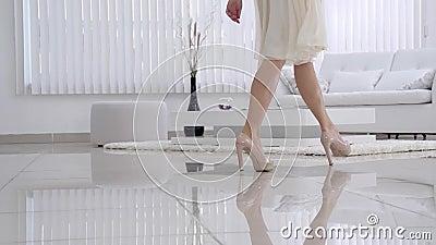 Pés bonitos da moça nas sapatas que movem sobre o interior na sala de visitas no movimento lento Opinião a moça elegantemente a vídeos de arquivo