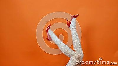 Pés fêmeas 'sexy' nas meias vermelhas do salto alto e da rede de pesca que levantam sobre o fundo alaranjado no estúdio Estilo re video estoque