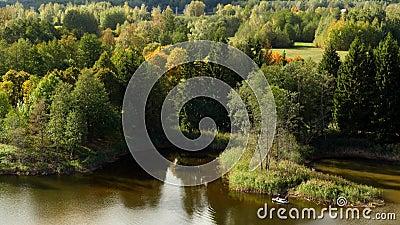 Pêcheur sur un canot en caoutchouc sur un lac, paysage d'automne banque de vidéos