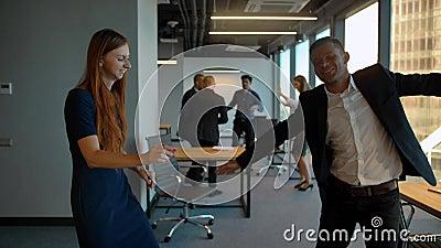 Paar in bedrijfsbureau die na het winnen van overeenkomst het vieren dansen stock video