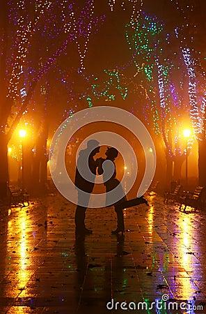 Paar dat bij steeg in nachtlichten loopt