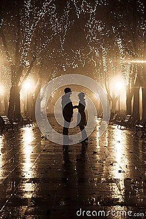 Paar dat bij steeg in nachtlichten loopt.