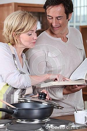 Paar dat een receptenboek gebruikt