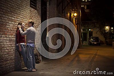 Paar dat tegen bakstenen muur op steegmanier leunt