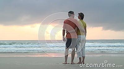 Paar die de zonsopgang op een strand overwegen stock video