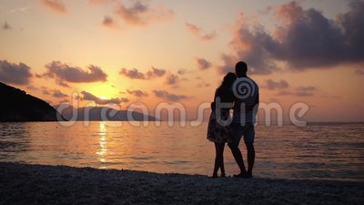 Paar die in liefde elkaar koesteren die zich op een strand bij zonsondergang over het overzees bevinden stock video