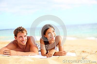 Paar die op strand gelukkig kijken