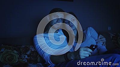Paar het letten op televisieprogramma in donkere ruimte stock footage