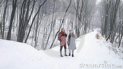 Paar in het midden van Forest Enjoying Snowfall stock videobeelden