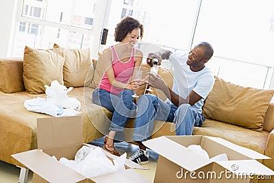 Paar met champagne door dozen in nieuw huis