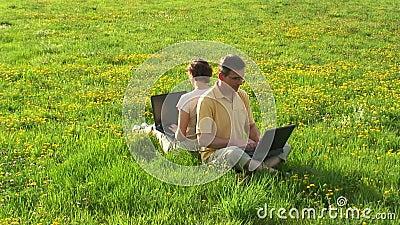 Paar met laptops op een weide stock videobeelden