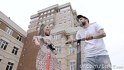 Paar staat op elektrische scooters en praat met een lage hoek stock video