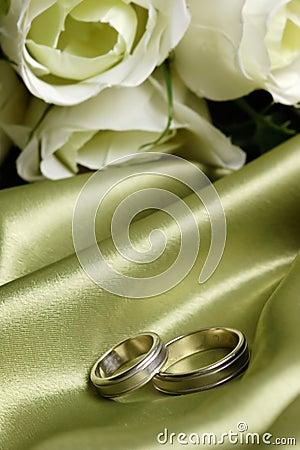 Paar trouwringen op groen satijn