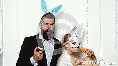 Paare in den Kaninchenkostümen mit Karotten und Apfel Sexy Häschenpaare auf weißem Hintergrund Pinupfrau, Weinlese, Blick stock video footage