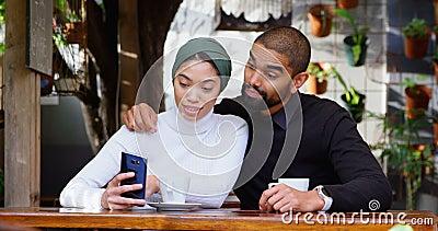 Paare, die über Handy in der Cafeteria 4k sich besprechen stock footage