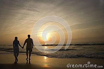 Paare, die auf Strand am Sonnenuntergang gehen