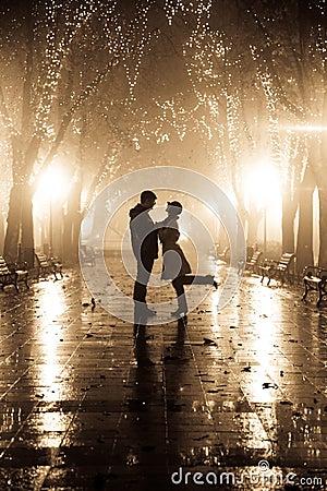 Paare, die an der Gasse in den Nachtleuchten gehen.