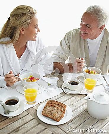 Paare, die gesundes Frühstück am Tisch genießen