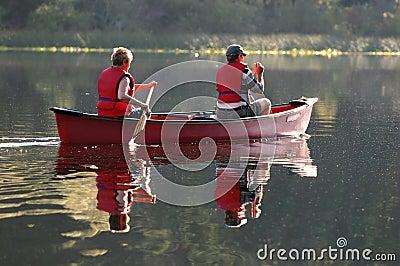 Paare, die Kanu schaufeln