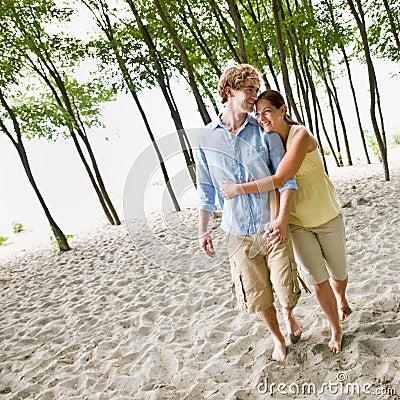Paare, die am Strand umarmen
