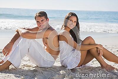 Paare, die zurück zu Rückseite auf dem Sand sitzen