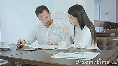 Paare von den Büroangestellten, die Menü betrachten und was entscheiden, an einer Kaffeestube zu bestellen stock footage