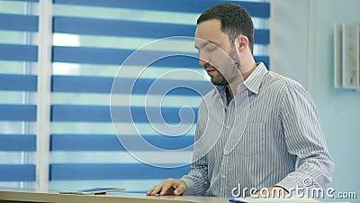 Paciente masculino impaciente que espera na mesa de recepção filme