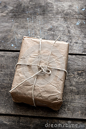 Package wrapped in wrinkled brown paper lying on weathered wood