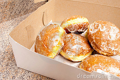Paczkis in a box on countertop.