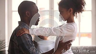 Padre africano di amore che abbraccia poca ragazza nera del bambino che esprime cura stock footage