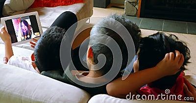 Padre e figli che per mezzo della compressa mentre sedendosi sul sofà 4k stock footage