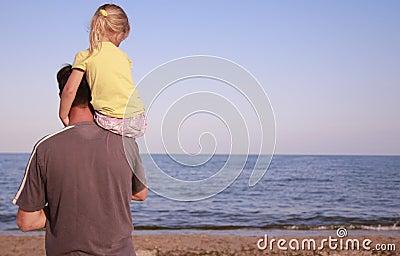 Padre e hija en la orilla de mar