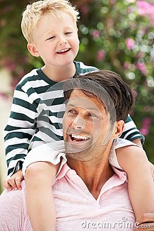 Padre que da paseo del hijo en hombros al aire libre