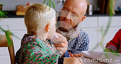 Padre que limpia su boca del hijo con el paño en casa 4k de la servilleta almacen de metraje de vídeo